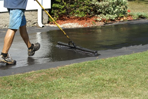 Worker Applying Driveway Sealer