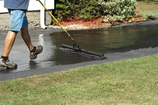 Worker Applying Driveway Sealer